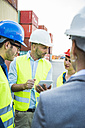 Four people with safety helmets and digital tablet talking at container port - UUF004468