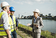 Businesswoman talking to people with safety helmets at riverside - UUF004472