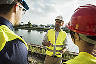 Woman and two men with safety helmets talking at riverside - UUF004475