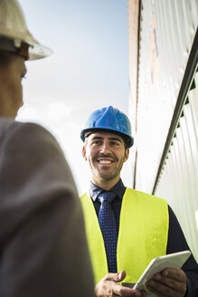 Businesswoman and smiling man with safety helmets at container port - UUF004480