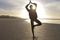 South Africa, Cape Town, silhouette of young woman doing tree pose on the beach - ZEF005202