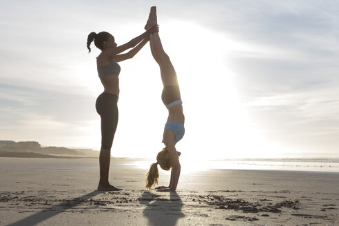 South Africa, Cape Town, young woman helping her friend doing handstand on the beach - ZEF005209
