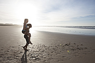South Africa, Cape Town, young woman giving her friend a piggy back on the beach - ZEF005215