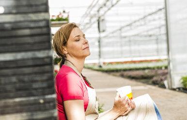 Woman in nursery having a coffee break - UUF004363