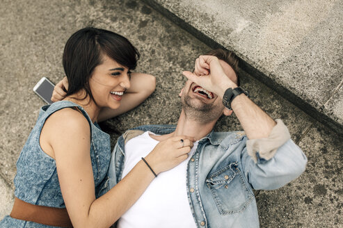 Laughing young couple lying on the ground outside - MGOF000247