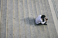 Young man sitting on stairs looking at cell phone - ABZF000062