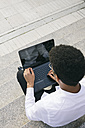 Young man sitting on stairs using a laptop - ABZF000064