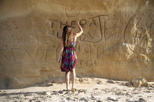 South Africa, woman carving her name on rock face - TOYF000962