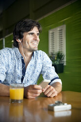 Portrait of smiling man hearing music with smartphone in a cafe - TOYF000974