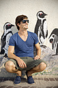 South Africa, smiling man wearing sunglasses leaning at facade with mural - TOY000979