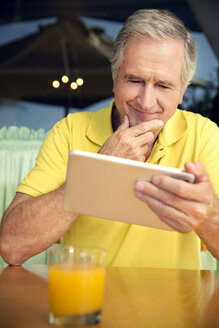 Portrait of senior man sitting in a cafe using digital tablet - TOYF000997