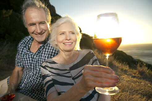 South Africa, happy senior couple with glasses of red wine by sunset - TOYF001003