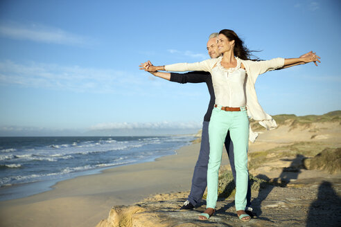 South Africa, couple with outstretched arms standing on the beach looking at distance - TOYF001006