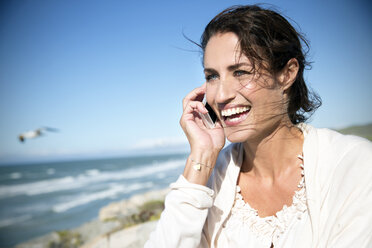 South Africa, portrait of smiling woman telephoning with smartphone in front of the sea - TOYF001009