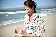 South Africa, portrait of smiling woman looking at shells in her hand - TOYF001015