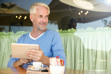 Portrait of smiling man with digital tablet - TOYF001021