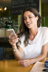 Portrait of smiling woman looking at her smartphone in a cafe - TOYF001024