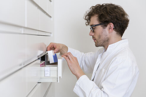 Pharmacist taking drug from a drawer cabinet - FKF001063