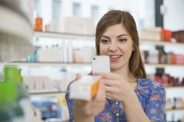Portrait of woman comparing products in a pharmacy - FKF001076