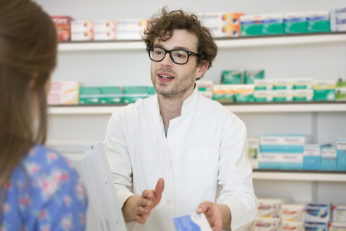 Portrait of pharmacist advising female customer - FKF001083