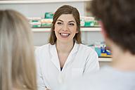 Portrait of smiling female pharmacist advising customers - FKF001088