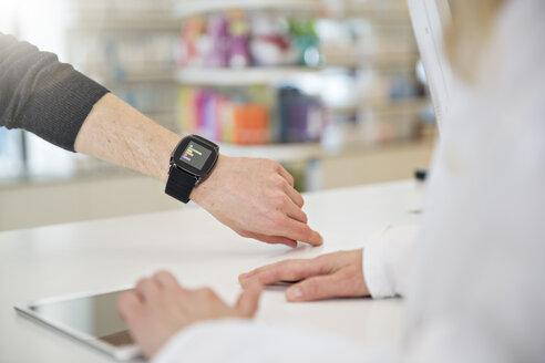 Customer showing female pharmacist his smartwatch - FKF001094