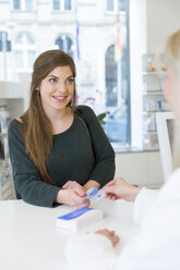Portrait of female customer paying cashless in a pharmacy - FKF001109