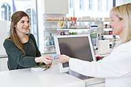 Portrait of female customer paying cashless in a pharmacy - FKF001111