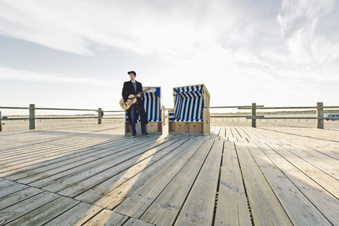 Germany, Sankt Peter-Ording, teenage boy with guitar standing in front of hooded beach chair - MSF004569