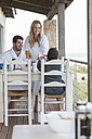 Family on patio of beach house eating breakfast - ZEF005349