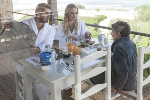 Family on patio of beach house eating breakfast - ZEF005352