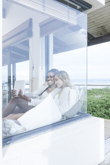 Two young women with digital tablet relaxing in beach house - ZEF005387