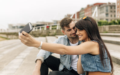 Spain, Gijon, young couple in love taking selfie with smartphone - MGOF000251