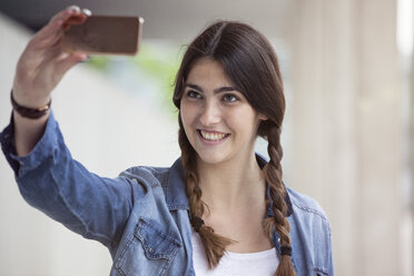 Young woman with braids taking a selfie with smartphone - RBF002883