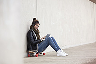 Young woman sitting on her longboard with digital tablet hearing music with headphones - RBF002889