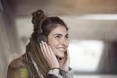 Portrait of smiling young woman hearing music with headphones - RBF002892