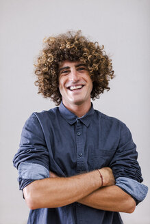 Portrait of smiling man with curly hair and crossed arms - EBSF000858