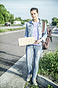 Germany, portrait of female hitchhiker with sign 'future' waiting at roadside - RIBF000110
