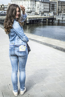 Netherlands, Amsterdam, female tourist with city map in her trouser pocket - RIBF000071