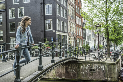 Netherlands, Amsterdam, female tourist standing on footbridge - RIBF000075