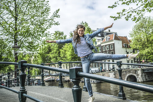 Netherlands, Amsterdam, female tourist balancing on one leg on a footbridge - RIBF000076