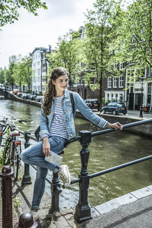 Netherlands, Amsterdam, female tourist lwith city map in front of town canal - RIBF000079