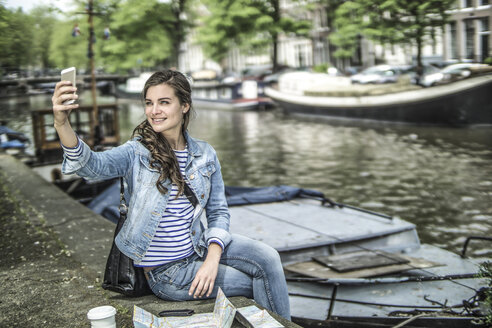 Netherlands, Amsterdam, female tourist having a rest taking a selfie in front of town canal - RIBF000111
