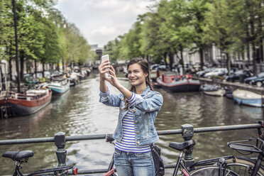 Netherlands, Amsterdam, female tourist taking a selfie with smartphone in front of town canal - RIBF000080