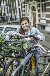 Netherlands, Amsterdam, smiling woman leaning on her bicycle - RIBF000095