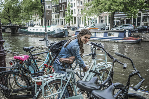 Netherlands, Amsterdam, smiling woman locking her bicycle in front of town canal - RIBF000097