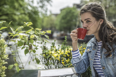 Netherlands, Amsterdam, woman drinking cup of coffee in a street cafe - RIBF000100
