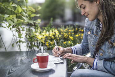 Netherlands, Amsterdam, woman writing postcards in a street cafe - RIBF000102