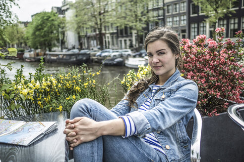 Netherlands, Amsterdam, portrait of female tourist having a rest in a street cafe - RIBF000104