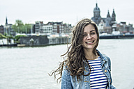 Netherlands, Amsterdam, portrait of smiling female tourist - RIBF000107